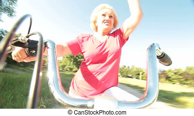 Happy senior woman riding bicycle waves his hand smiling