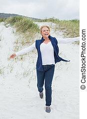 Happy senior woman running at beach