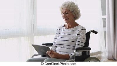 Happy senior woman sit on wheelchair using digital tablet