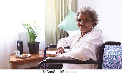 Happy senior woman sitting in wheelchair at nursing home