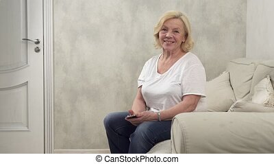 Happy senior woman sitting on a couch