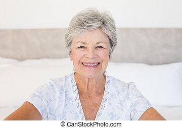 Happy senior woman sitting on bed