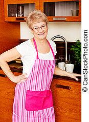 Happy senior woman standing in kitchen