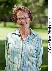 Happy senior woman standing in park