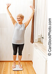 Happy senior woman standing on weight scale in living room