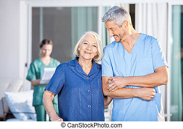 Happy Senior Woman Standing With Male Caretaker