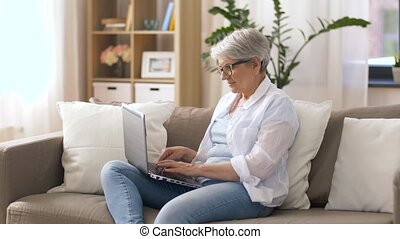 happy senior woman typing on laptop at home - technology,...