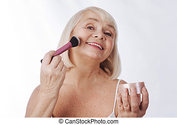 Happy senior woman using a cosmetic brush