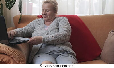 Happy senior woman using computer sitting on sofa