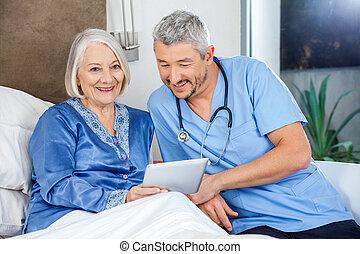 Happy Senior Woman Using Tablet PC With Caretaker