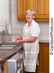 happy senior woman washing dishes
