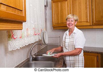 senior woman washing dishes