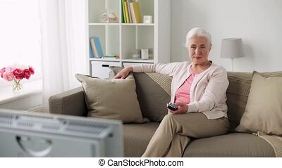 happy senior woman watching tv at home