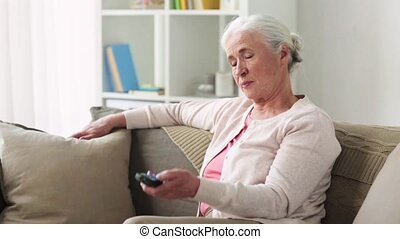 happy senior woman watching tv at home - television,...