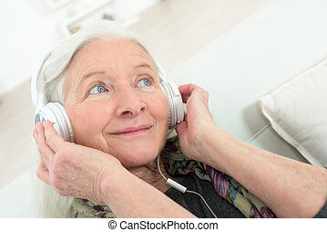 happy senior woman wearing headphones