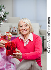 Happy Senior Woman With Christmas Gift