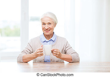 happy senior woman with cup of tea or coffee