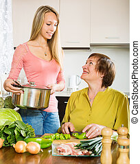 Happy senior woman with  daughter cooking  together