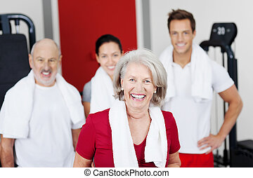 Happy Senior Woman With Family At Gym