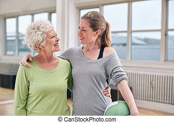 Happy senior woman with her personal trainer at gym