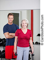 Happy senior woman with her trainer at the gym