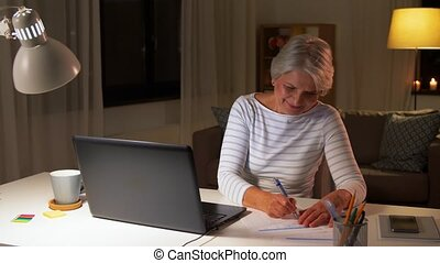 happy senior woman with laptop at home in evening -...