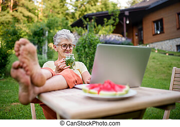 Happy senior woman with laptop working outdoors in garden, home office concept.