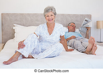 Happy senior woman with man on bed