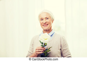 happy senior woman with rose flower at home