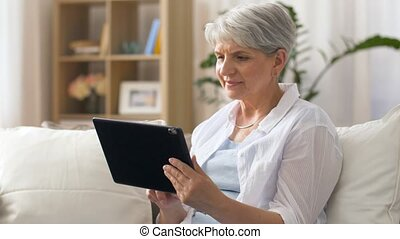happy senior woman with tablet pc at home - technology, age...