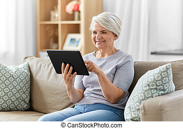 happy senior woman with tablet pc at home