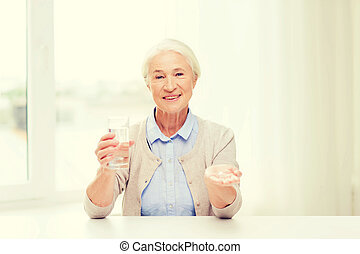 happy senior woman with water and medicine at home - age,...