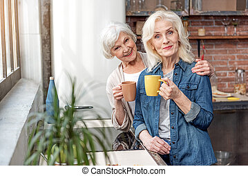 Happy senior women relaxing with cup of hot beverage