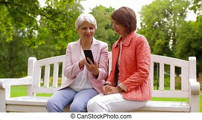 happy senior women with smartphone at summer park -...