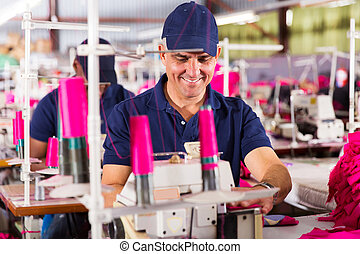 senior worker sewing in clothing factory