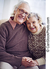 Happy seniors - Cheerful senior couple in sweaters looking...