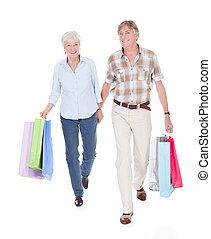 Seniors Couple Walking With Shopping Bag