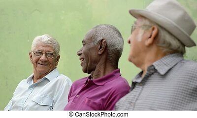 Active retirement and senior people, group of three elderly male friends talking and laughing on bench in public park. Sequence