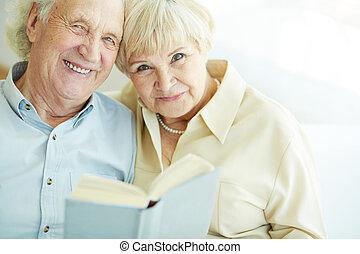 Happy seniors - Portrait of a candid senior couple reading...