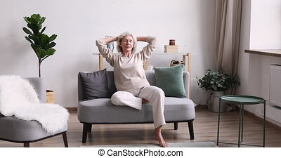 Happy serene senior adult woman relaxing on comfortable couch. Smiling healthy old lady enjoying retirement slow life in modern cozy living room interior. Relaxed elder european grandma resting at home