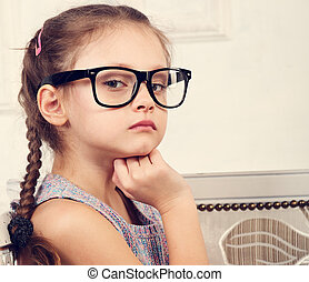 Happy serious calm kid girl in eyeglasses looking and thinking about with fun face. Closeup toned portrait