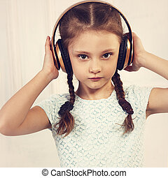 Happy calm kid girl in blue dress listening the music in