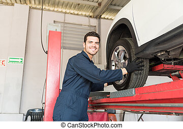 Happy Serviceman Removing Tire By Lift In Garage