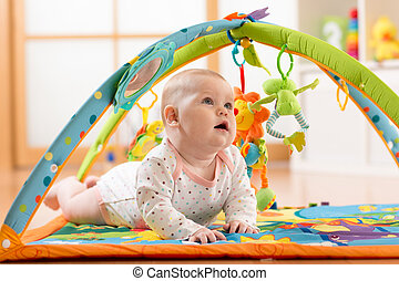 Happy seven months baby girl plays lying on colorful playmat