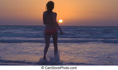 Happy sexy girl is running to sunset on the beach in the sea. Young woman in pink bikini runs in the calm ocean, jumping on the waves splashing water under beautiful sky. Slow motion