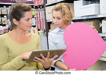 happy shop assistant with tablet pc helping woman