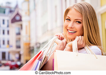 Happy shopaholic girl. Beautiful young cheerful woman holding shopping bags and looking at camera while standing outdoors