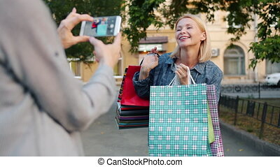 Happy shopaholic mature lady is posing for smartphone camera holding shopping bags outdoors while friend taking picture. Photography and consumerism concept.