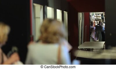 Rear view of two attractive women holding many clothes, entering fitting room in fashion boutique shop. Two senior female friends with apparels reflected in big mirror coming into fitting room in clothing store.