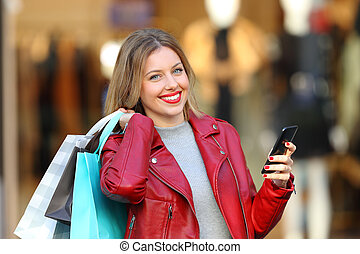Happy shopper holding bags and phone looking at camera